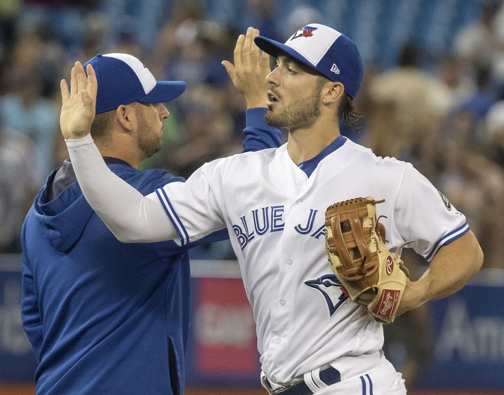 Toronto Blue Jays' Randall Grichuk high-fives with teammates after they defeated the Boston Red Sox 8-5 in a baseball game Thursday, Aug. 9, 2018, in