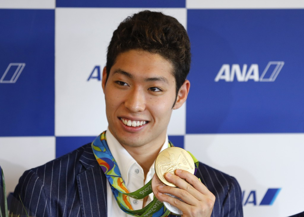 FILE - In this Aug. 17, 2016, file photo, Rio 2016 Summer Olympic Games men's 400 medley gold medalist Kosuke Hagino of Japan shows his medals for pho