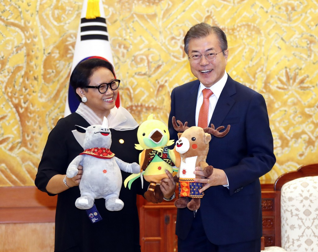 In this July 27, 2018, photo, South Korean President Moon Jae-in, right, and Indonesian Foreign Minister Retno Marsudi hold the mascots of the 2018 As