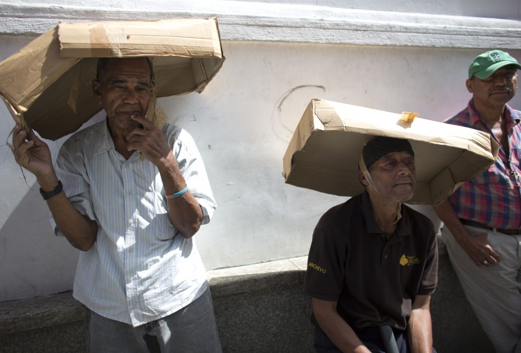In this Friday, Aug. 3, 2018 photo, men utilize cardboard boxes to shade themselves from the sun's rays as they wait in line to take part in a vehicle