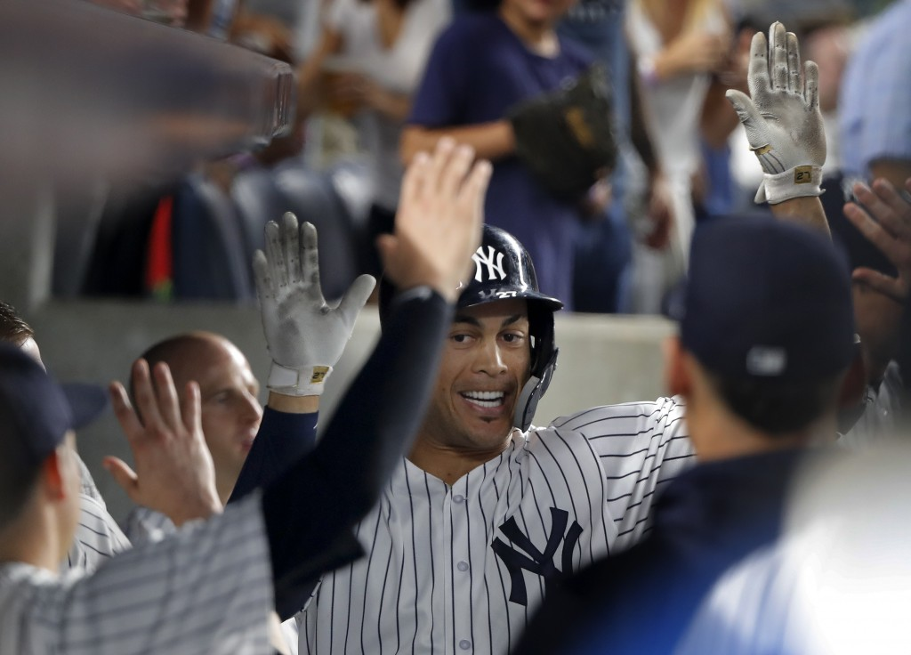 New York Yankees' Giancarlo Stanton celebrates with teammates after hitting a solo home run against the Texas Rangers during the fifth inning of a bas