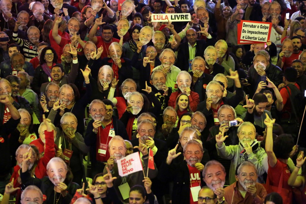 In this Saturday, Aug. 4, 2018 photo, supporters wears masks depicting Brazil's former President Luiz Inacio Lula da Silva during the Workers Party na