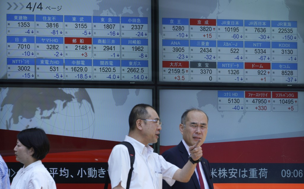 Men stand in front of an electronic stock board showing Japan's Nikkei 225 index at a securities firm in Tokyo Friday, Aug. 10, 2018. Shares were lowe