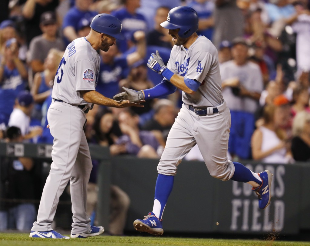 Los Angeles Dodgers third base coach Chris Woodward, left, congratulates Chris Taylor, who heads for home on a solo home run off Colorado Rockies reli