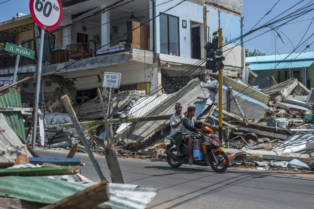 In this Friday, Aug. 10, 2018, photo, motorists ride past buildings ruined by Sunday's earthquake in Pamenang, Lombok Island, Indonesia. The north of