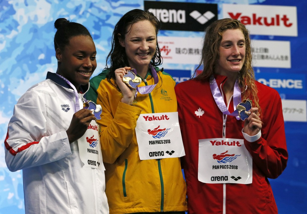 Australia's Cate Campbell, center, poses with her medal on the podium after winning the women's 100m freestyle final with second-placed Simone Manuel,