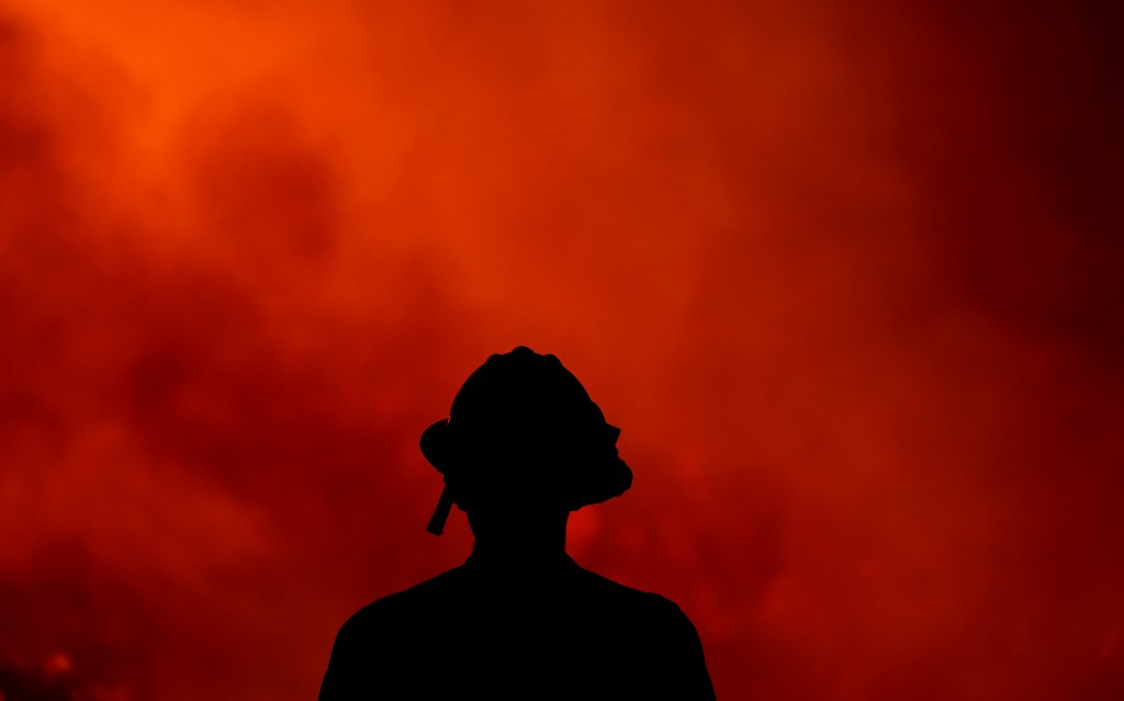 A firefighter keeps watch on the Holy Fire burning in the Cleveland National Forest in Lake Elsinore, Calif., Thursday, Aug. 9, 2018. (AP Photo/Ringo