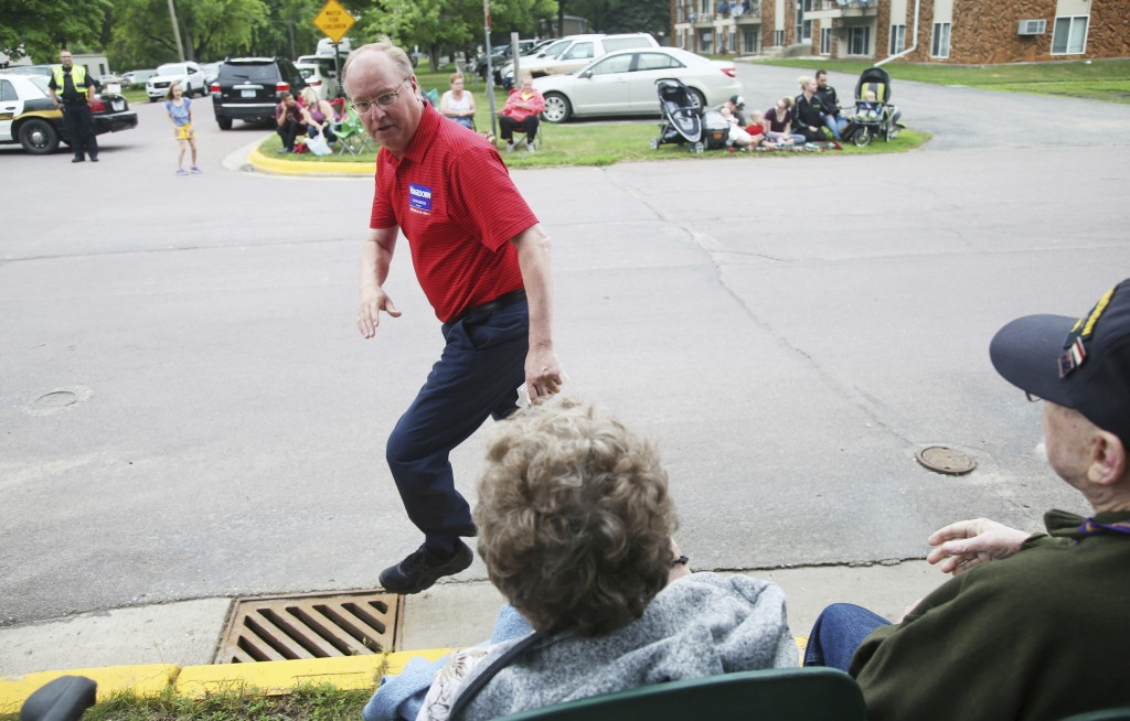 In this June 10, 2018 photo, Minnesota 1st District congressional candidate Jim Hagedorn jogs pas parade goers in Waterville, Minn. Waterville's 54th