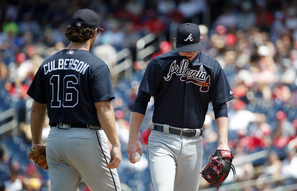 Atlanta Braves shortstop Charlie Culberson looks on as relief pitcher Wes Parsons pauses on the mound during the third inning of a baseball game again