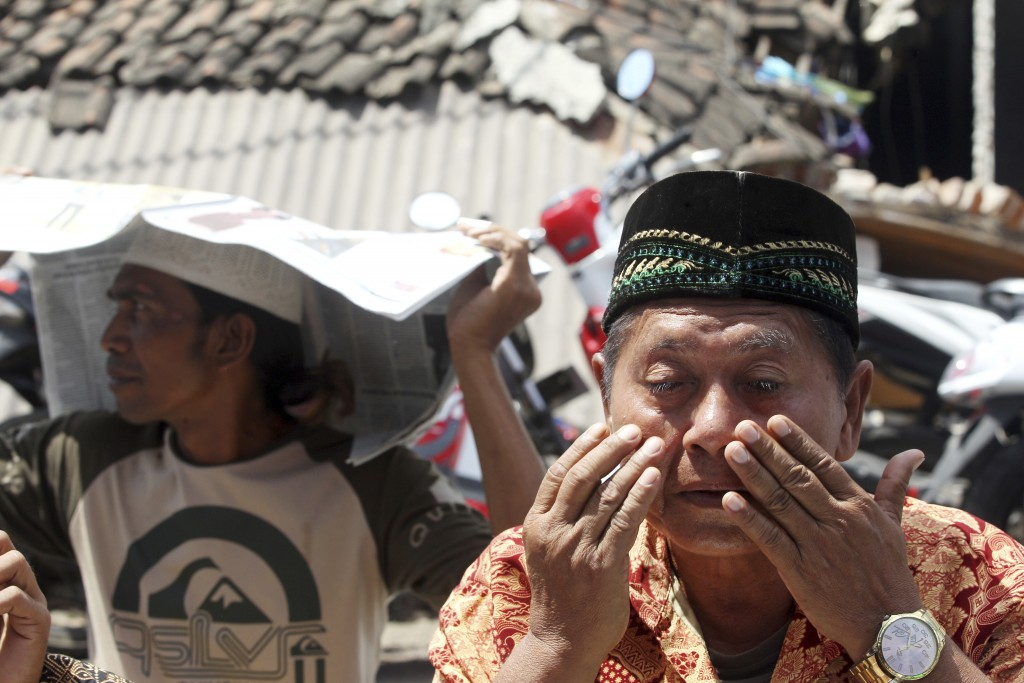 A man weeps as he prays during Muslim Friday prayers in North Lombok, Indonesia, Friday, Aug. 10, 2018. The north of Lombok was devastated by a powerf