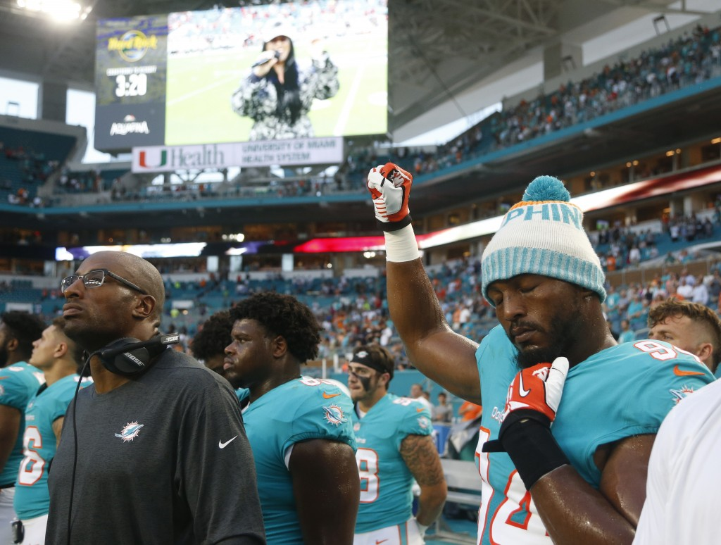 Miami Dolphins defensive end Robert Quinn (94) raises his right fist during the singing of the national anthem, before the team's NFL preseason footba