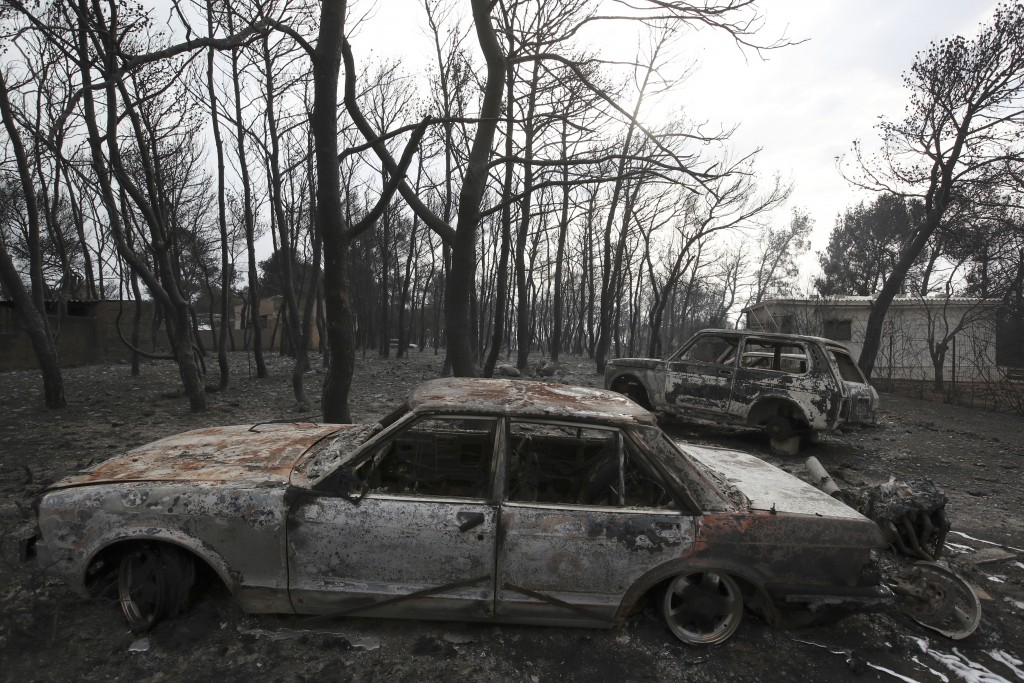 FILE - In this file photo dated Tuesday, July 24, 2018, burned cars are seen outside a damaged house in Rafina, east of Athens, after wildfires raged