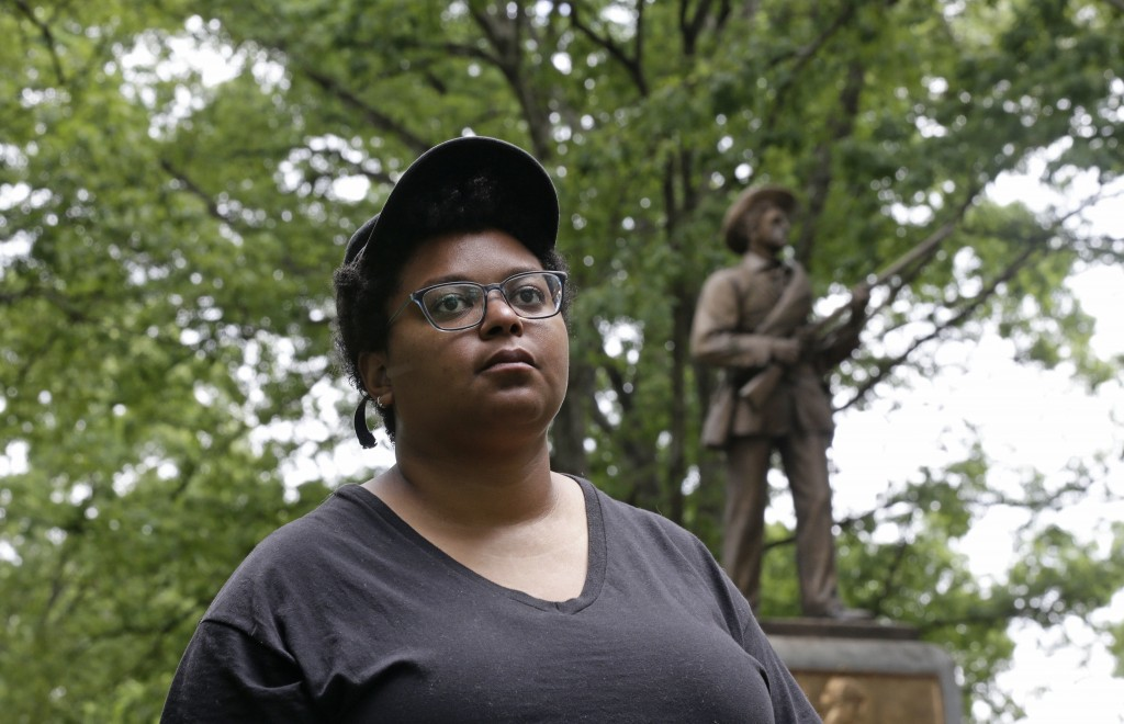 "Activist Maya Little stands near the ""Silent Sam"" Confederate statue on campus at the University of North Carolina in Chapel Hill, N.C., on Tuesday, M"