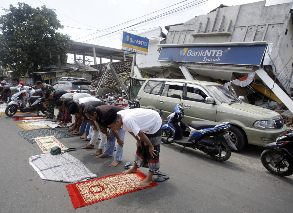 Villagers attend Muslim Friday prayers as damaged buildings by an earthquake are seen in the background in North Lombok, Indonesia, Friday, Aug. 10, 2
