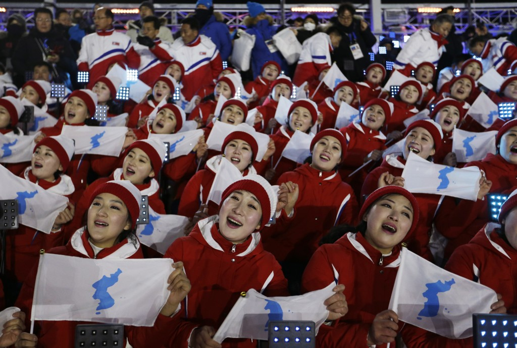 FILE - In this Feb. 9, 2018, file photo, members of the North Korean delegation hold flags of the combined Koreas before the opening ceremony of the 2