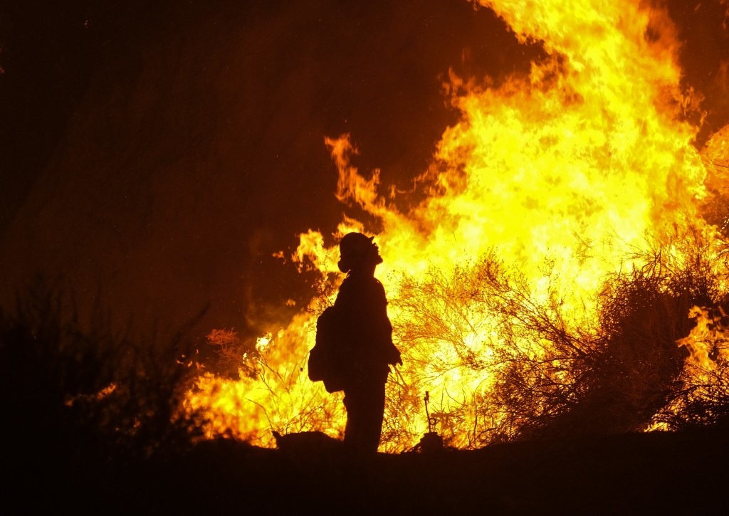 A firefighter keeps watch as the Holy Fire burns in the Cleveland National Forest along a hillside at Temescal Valley in Corona, Calif., Thursday, Aug