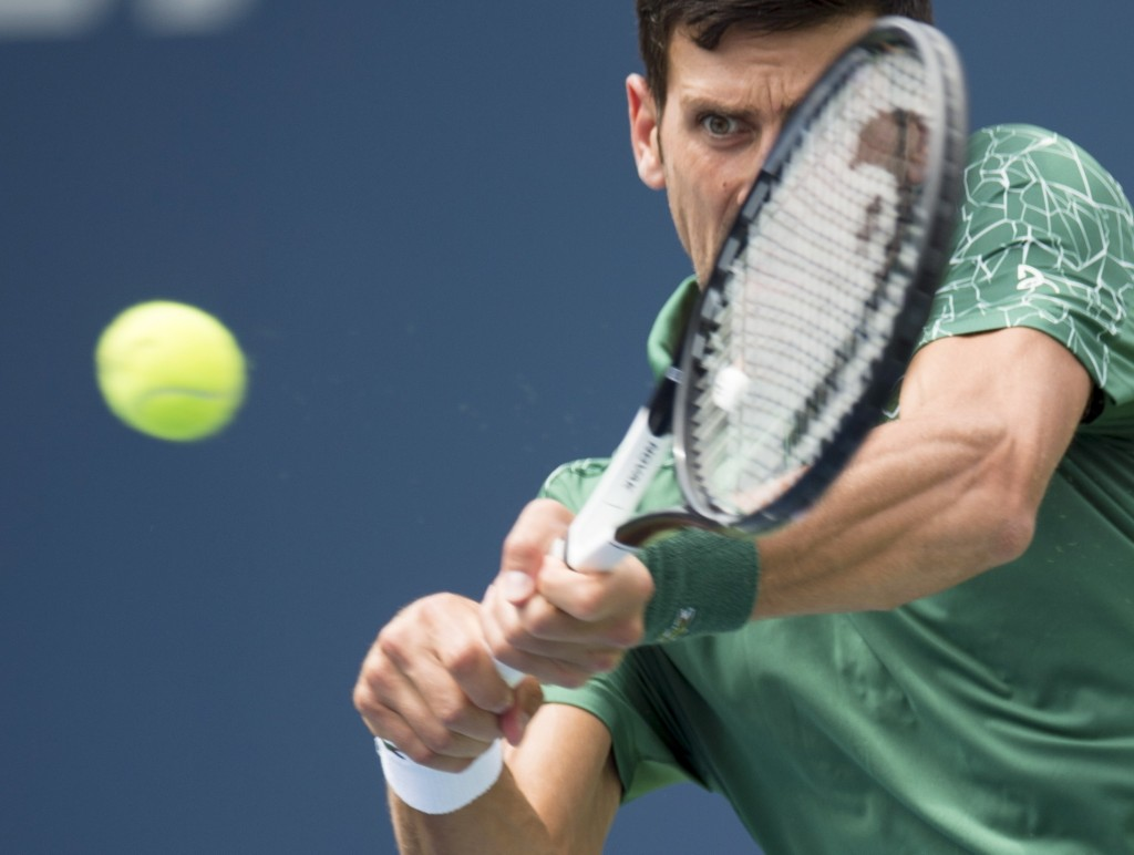 Novak Djokovic, of Serbia, makes a return to Stefanos Tsitsipas, of Greece, during the Rogers Cup men's tennis tournament in Toronto, Thursday, Aug. 9