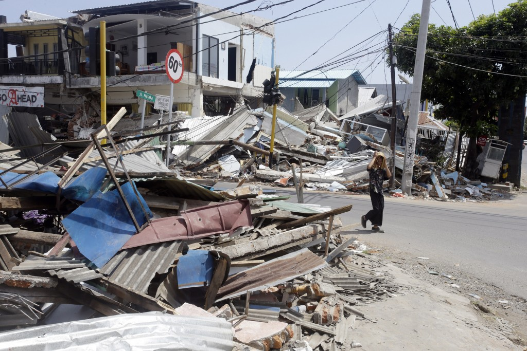 A man walks past destroyed buildings in North Lombok, Indonesia, Friday, Aug. 10, 2018. The north of Lombok was devastated by the powerful quake that