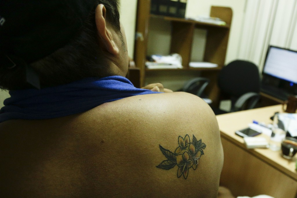 In this July 24, 2018 photo, a university student who did not want to be identified for fear of reprisals from the government show his tattoo of a Sac