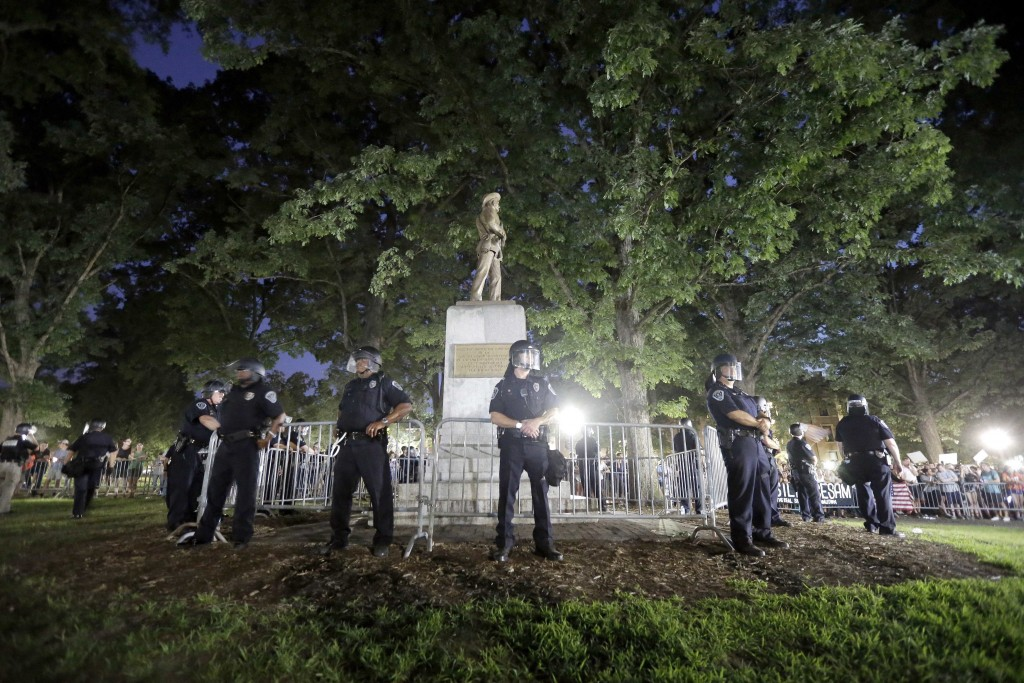 "FILE - In this Tuesday, Aug. 22, 2017 file photo, police surround the ""Silent Sam"" Confederate monument during a protest to remove the statue at the U"