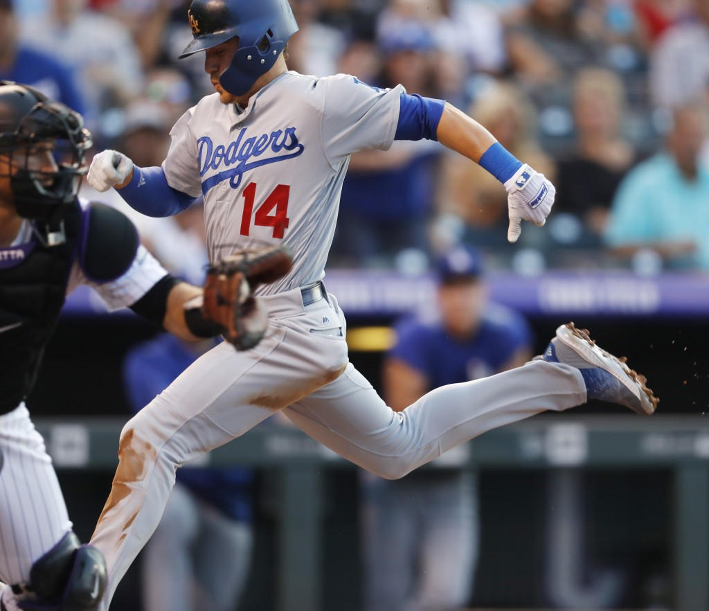 Los Angeles Dodgers' Enrique Hernandez (14) scores on a sacrifice fly hit by Chris Taylor as Colorado Rockies catcher Chris Iannetta fields the throw