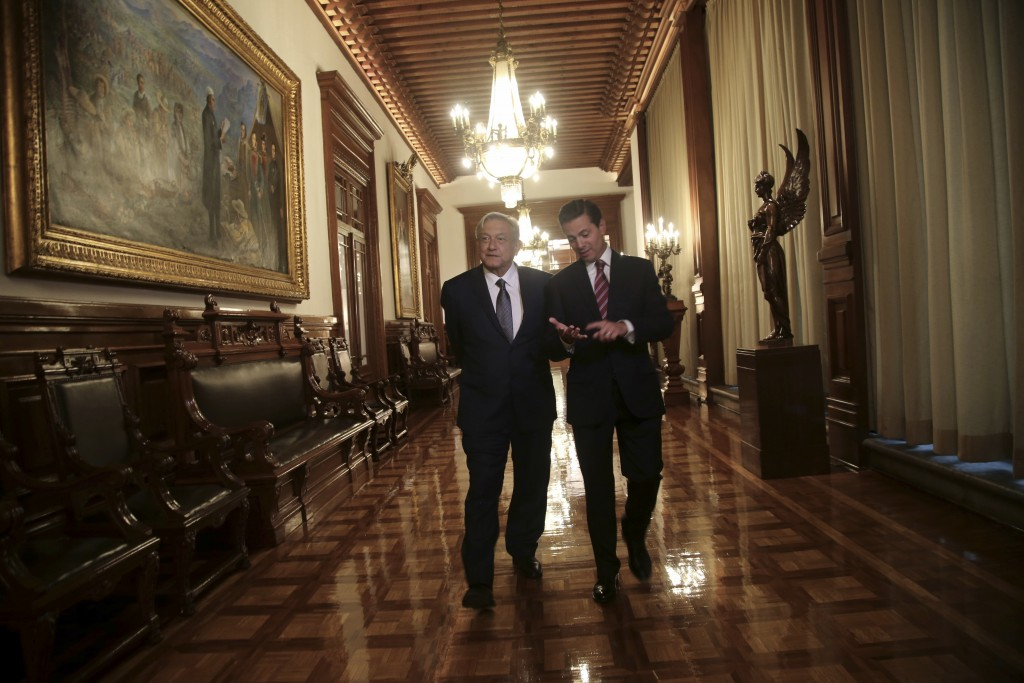 In this photo released by the press office of Mexico's President-elect Andres Manuel Lopez Obrador, Mexican President Enrique Pena Nieto, right, walks
