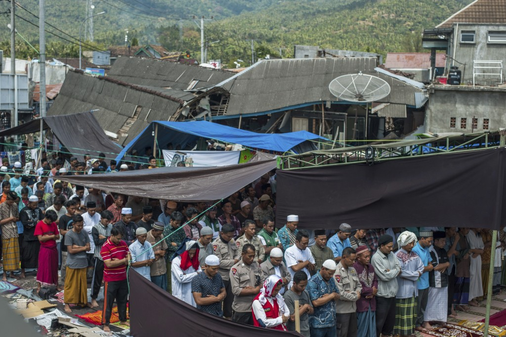 Muslim men perform Friday prayer as houses ruined by Sunday's earthquake are seen in the background at a makeshift mosque in Pamenang, Lombok Island, ...