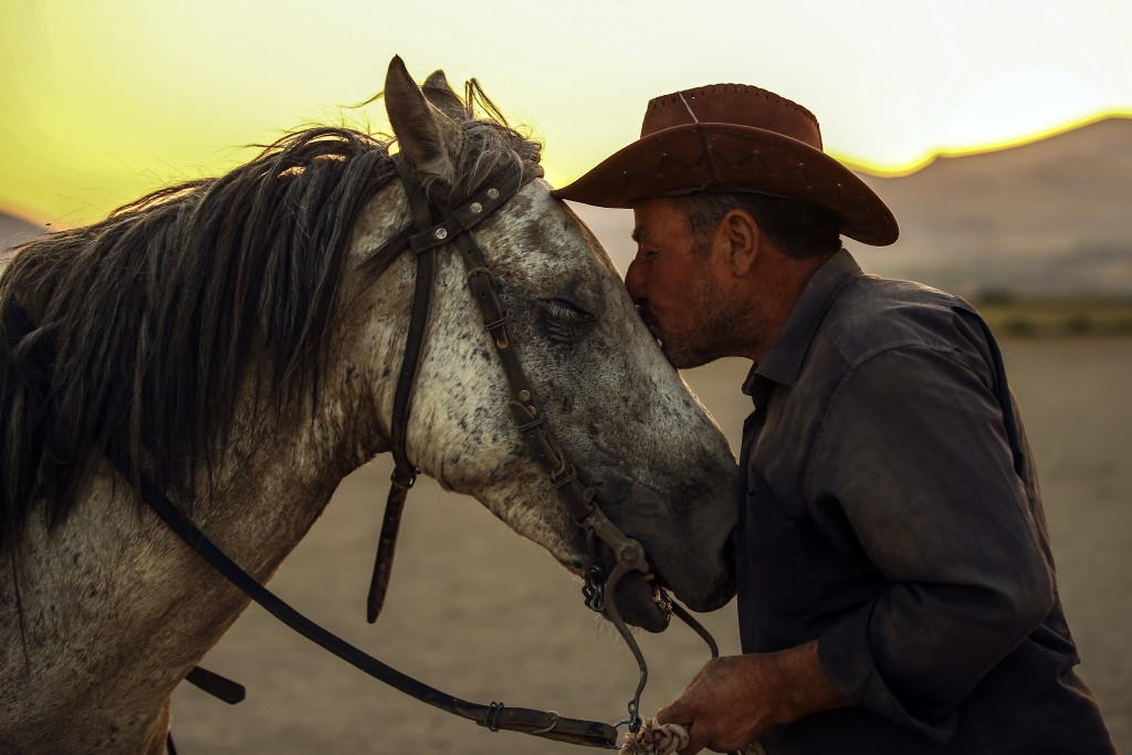 In this photo taken on Sunday, Aug. 5, 2018, Ali Kemer, a 50-year-old horse-breeder, kisses one of his horses in the village of Hormetci, on the footh