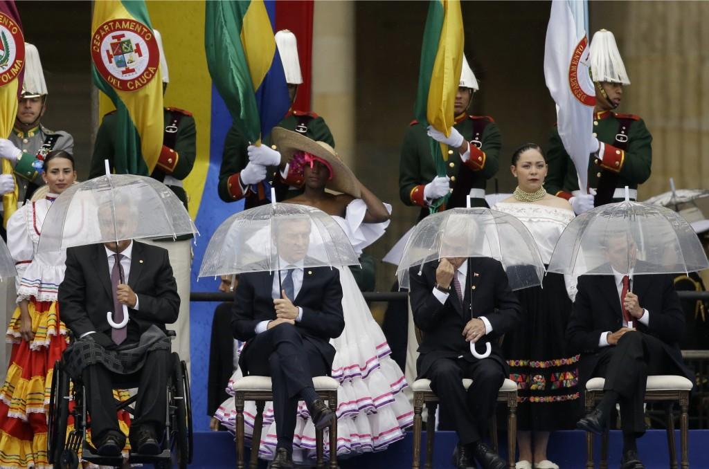 In this rainy Tuesday, Aug. 7, 2018 photo, Ecuador's President Lenin Moreno, from left, Argentina's President Mauricio Macri, Chile's President Sebast