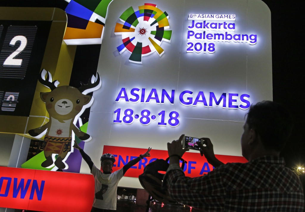 FILE - In this Aug. 18, 2017, file photo, a man has his photo taken at the one-year countdown clock to the 2018 Asian Games in Jakarta, Indonesia. The