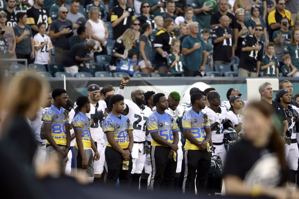 Philadelphia Eagles' Malcolm Jenkins, center left, raises his fist during the national anthem before the team's preseason NFL football game against th