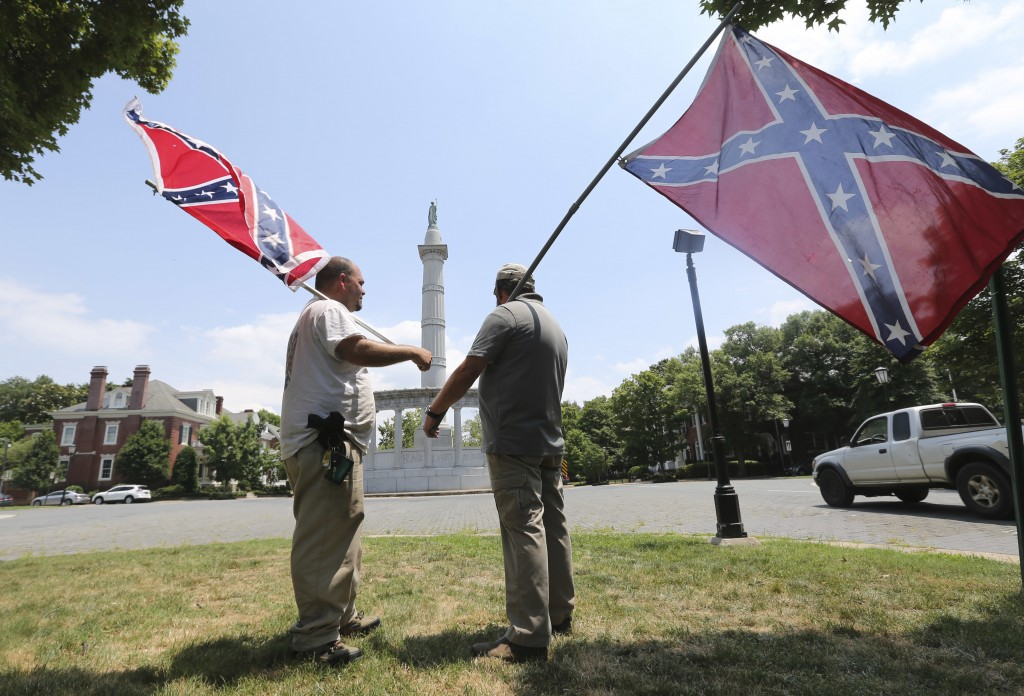 FILE - In this Thursday, June 25, 2015 file photo, activists hold Confederate flags near the monument for Confederate President Jefferson Davis on Mon