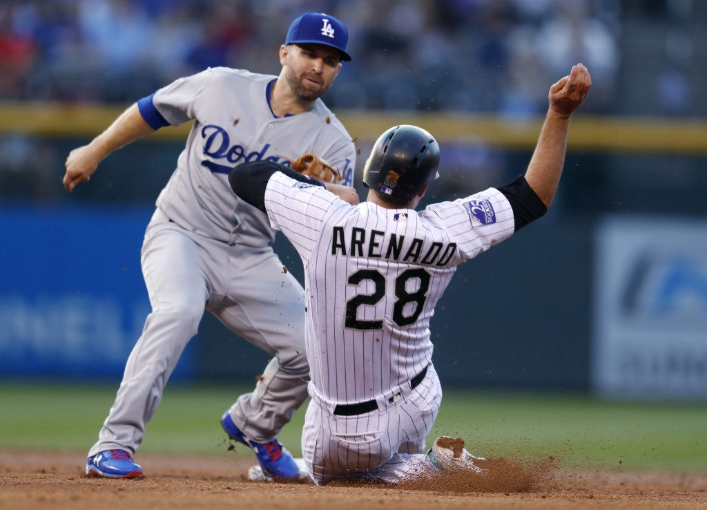 Los Angeles Dodgers second baseman Brian Dozier, left, applies the tag to put out Colorado Rockies' Nolan Arenado who was trying to steal second in th
