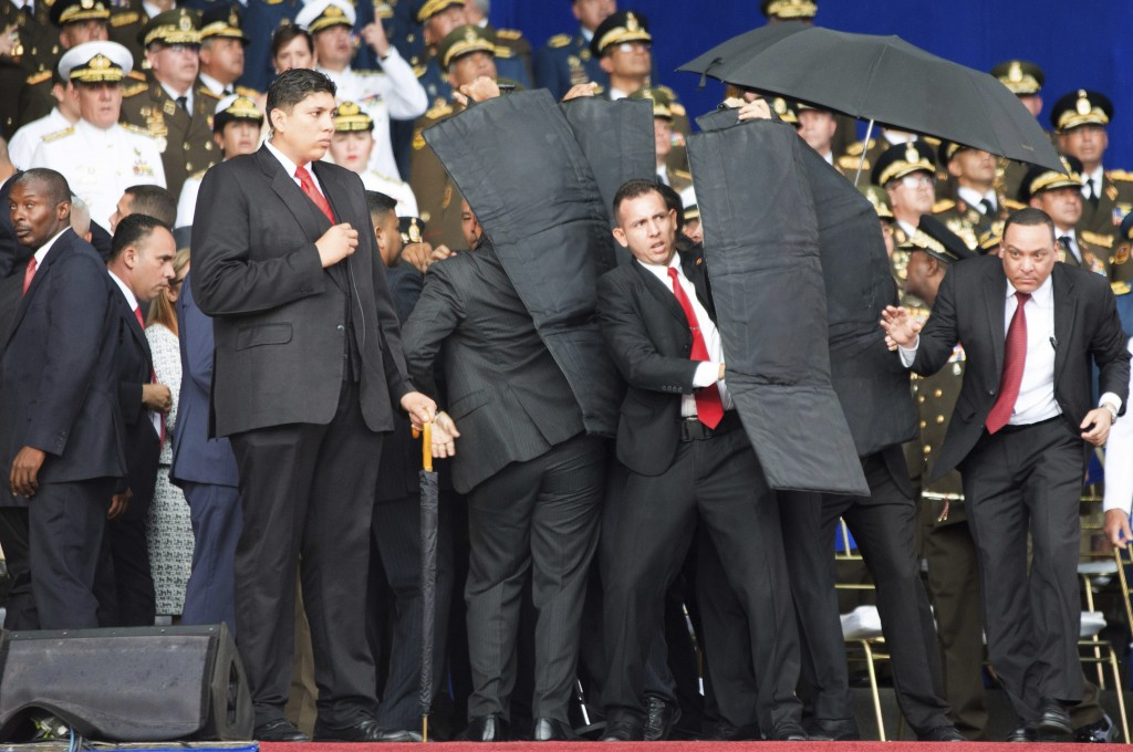 In this Saturday, Aug. 4, 2018 photo released by China's Xinhua News Agency, security personnel surround Venezuela's President Nicolas Maduro during a