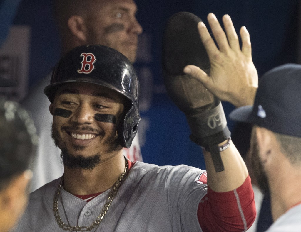 Boston Red Sox's Mookie Betts is congratulated in the dugout after scoring against the Toronto Blue Jays during the first inning of a baseball game Th