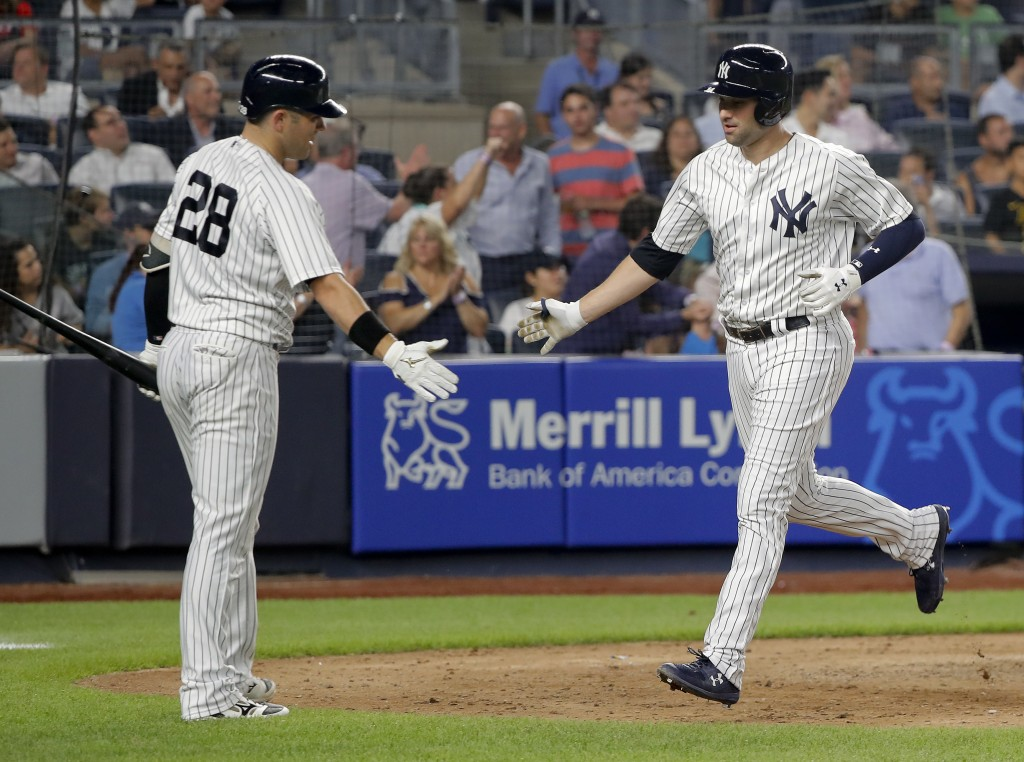 New York Yankees' Neil Walker, right, is congratulated by Austin Romine (28) after hitting a solo home run against the Texas Rangers during the sixth