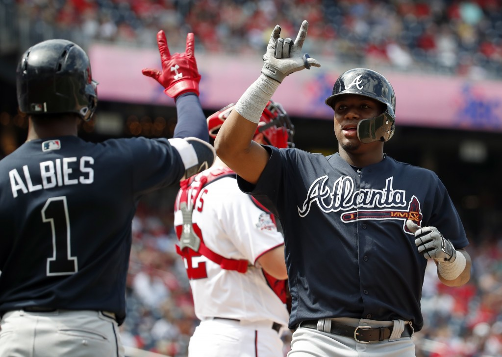 Atlanta Braves' Ozzie Albies celebrates with Ronald Acuna Jr., after Acuna's solo home run during the eighth inning of a baseball game at Nationals Pa