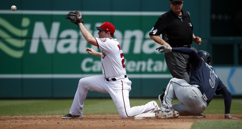 Atlanta Braves' Freddie Freeman slides into second base for a double as Washington Nationals second baseman Daniel Murphy waits for the throw during t