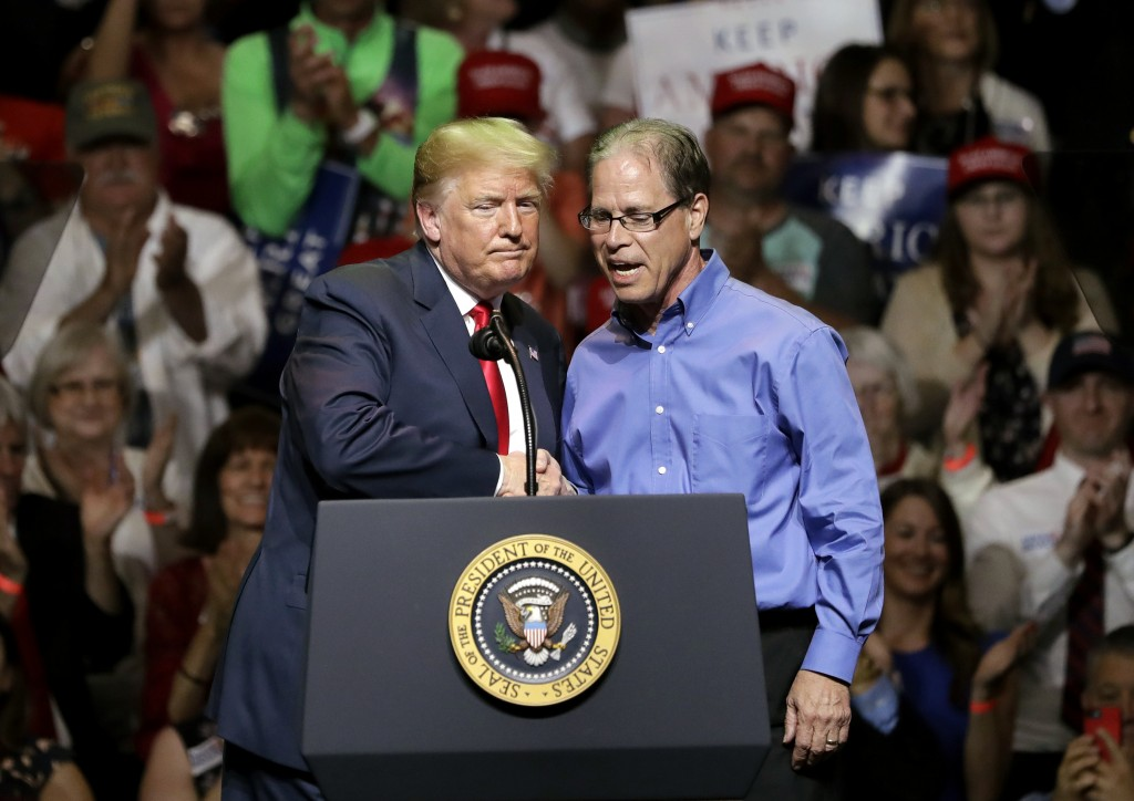 FILE - In this May 10, 2018 file photo, President Donald Trump, left, and Indiana Republican senatorial candidate Mike Braun shake hands as they embra