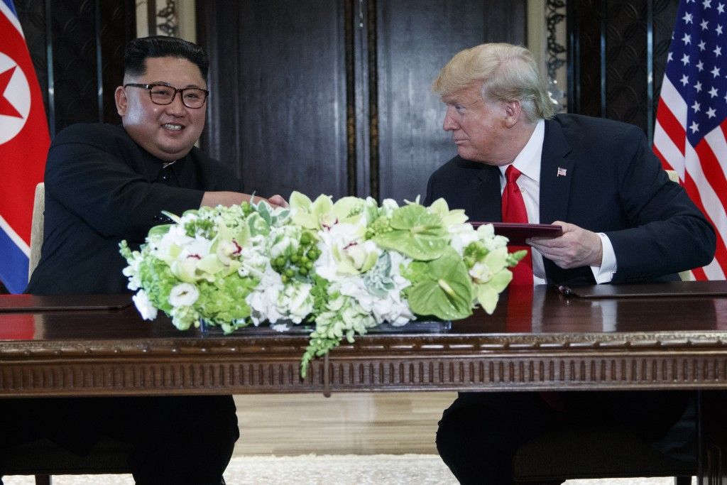FILE - In this June 12, 2018, file photo, U.S. President Donald Trump, right, and North Korean leader Kim Jong Un participate in a signing ceremony du