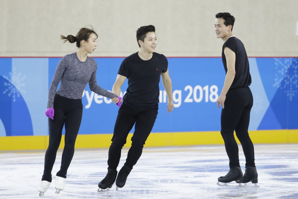 FILE - In this Feb. 5, 2018, file photo, North Korea's Kim Ju Sik, right, skates next to South Korea's Kim Kyueun, left, and Kam Alex Kang Chan during