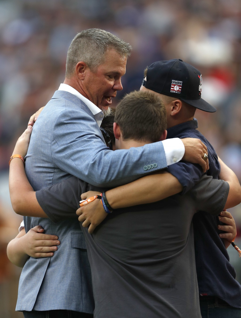 Former Atlanta Braves third baseman and Baseball Hall of Fame member Chipper Jones, left, hugs family members during a ceremony before a baseball game