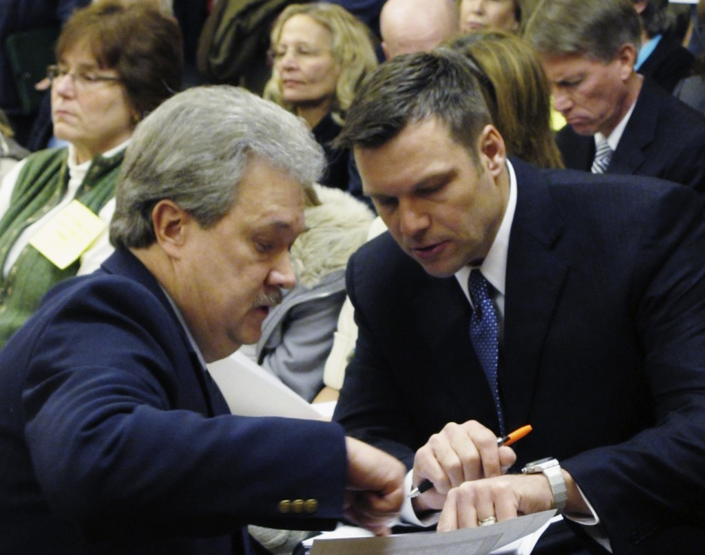 FILE - In this Jan. 31, 2011, file photo, Kansas Secretary of State Kris Kobach, right, confers with Assistant Secretary of State Eric Rucker during a