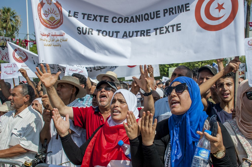 "People demonstrate with a banner reading ""Quran text before any other text"" during a demonstration in Tunis, Saturday Aug 11, 2018. Thousands of Musli"
