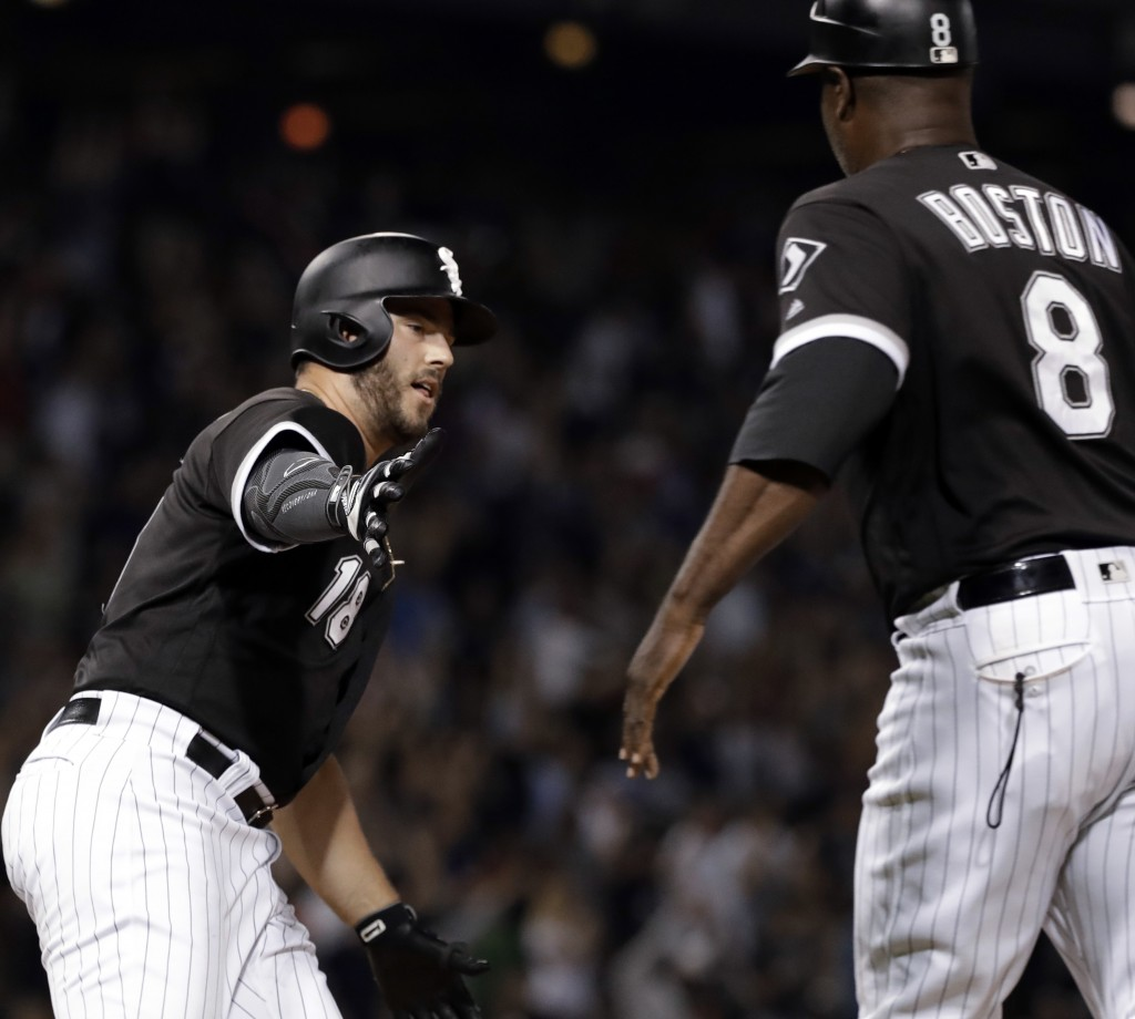 Chicago White Sox's Daniel Palka, left, celebrates with first base coach Daryl Boston as he rounds the bases after hitting the game-winning solo home
