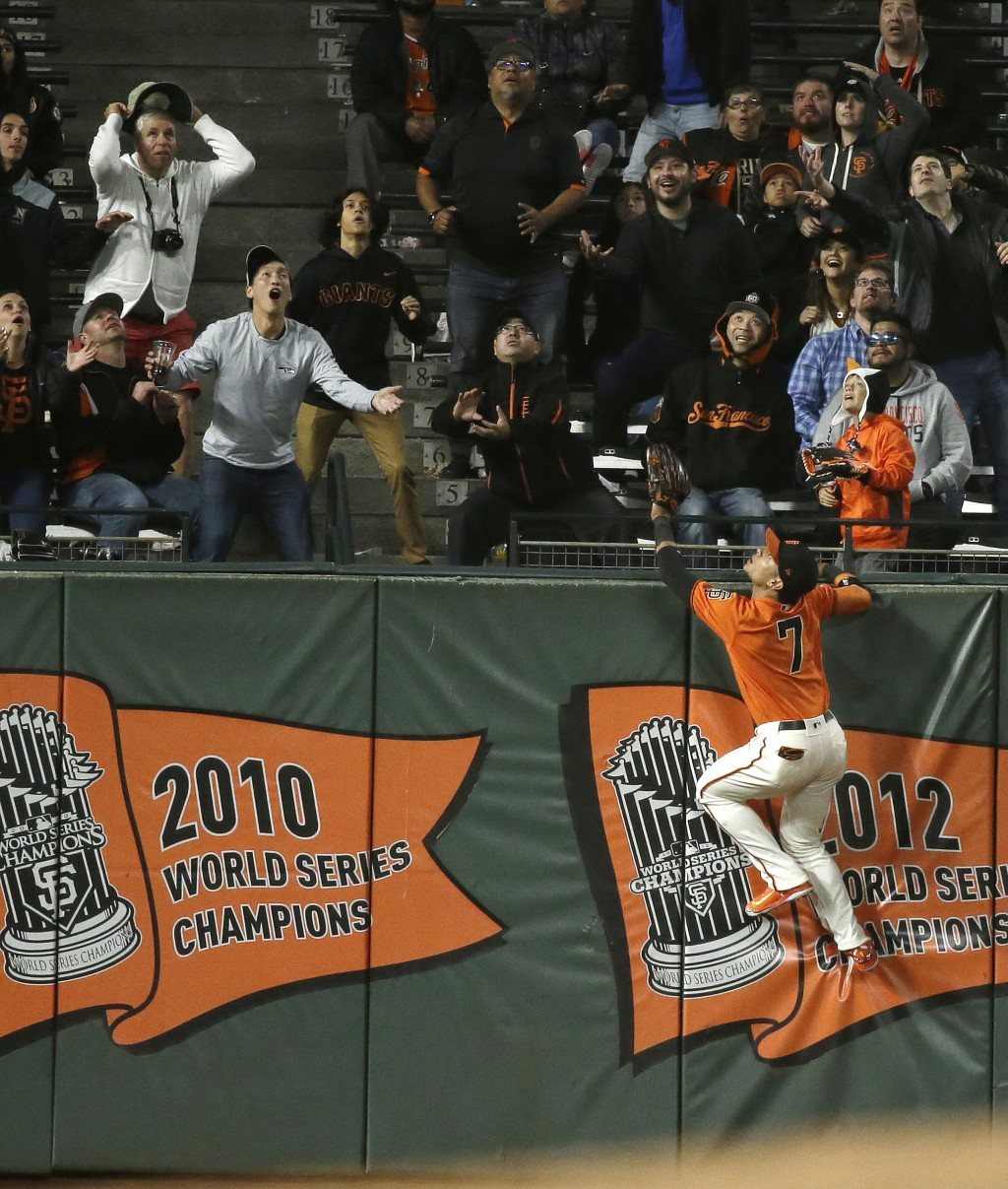 San Francisco Giants left fielder Gorkys Hernandez leaps up on the outfield wall and watches a home run hit by the Pittsburgh Pirates' Adeiny Hechavar