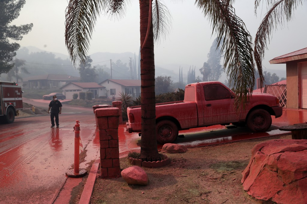 A truck and a street are covered in fire retardant dropped by an air tanker as crews battle a wildfire Friday, Aug. 10, 2018, in Lake Elsinore, Calif....
