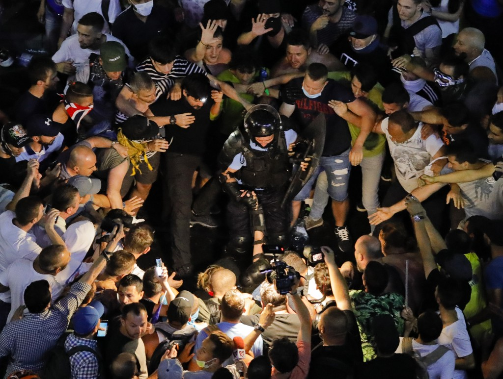 People surround fallen riot police officers during a charge to clear the square during protests outside the government headquarters, in Bucharest, Rom
