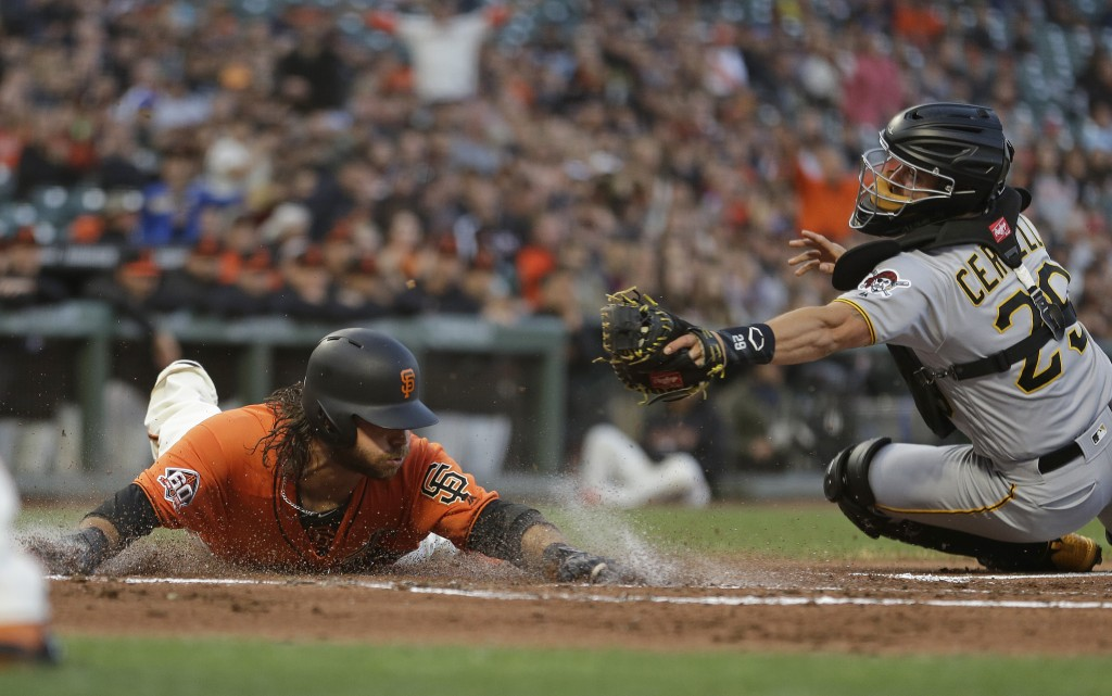 San Francisco Giants' Brandon Crawford slides into home plate to score the Giants' third run as Pittsburgh Pirates catcher Francisco Cervelli reaches