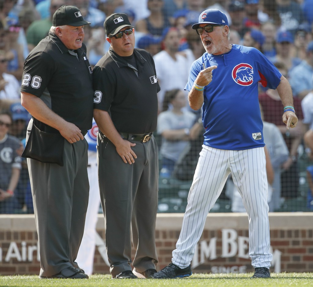Chicago Cubs manager Joe Maddon, right, argues a call against his team with umpire's Bill Miller, left, and Todd Tichenor, center, as he is ejected fr